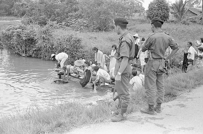 Armed soldiers stand guard in Sarawak in 1965 as a group of Chinese villagers take a communal bath. The authorities aim to protect the area from Indonesian raiders and to eliminate Communist influence.